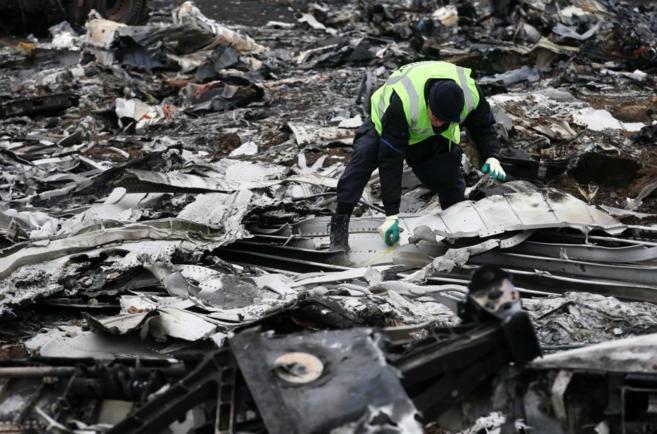 Un investigador holandés recoge restos del avión siniestrado MH17 de Malasysia Airlines. REUTERS