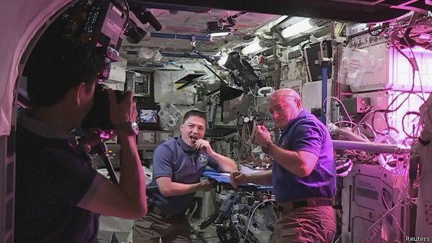 Los estadounidenses Kelly (der.) y Lindgren posan ante el japonés Yui quien registra la histórica mordida de una lechuga espacial. Crédito:Reuters