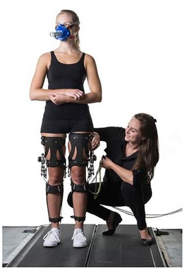 La autora principal del estudio, Jessica Selinger coloca un exoesqueleto, para monitorear los cambios en la marcha de la mujer durante los experimentos. Créditos: Greg Ehlers