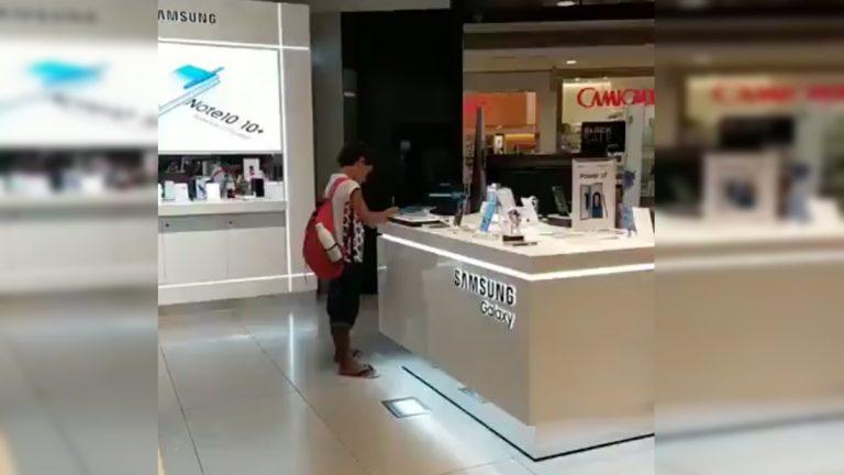 Niño usa tablet de exhibición en tienda de centro comercial para hacer su tarea