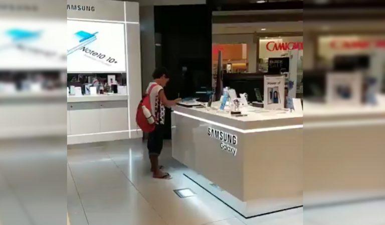 Niño usa tablet de exhibición de una tienda de centro comercial para hacer su tarea